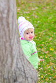 Small beautiful girl in green suit on green glade by autumn peers because o — Stock Photo