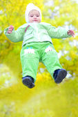 Small beautiful girl in green suit on green glade under yellow sheet autumn — Stock Photo