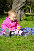 Small girl sits on green glade with apple — Stock Photo