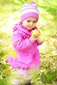 Het kleine meisje op een groene glade met een apple — Stockfoto