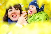 Små vackra pojken bland gula hösten lämnar med mamma — Stockfoto