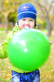 The little boy with a dummy and with a ball on a green glade — Stock Photo