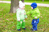 Two small children sit on a green clearing with yellow leaves — Stock Photo