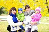 Duas crianças com as mães em uma clareira verde no outono — Fotografia Stock