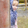 The small beautiful girl in a dark blue scarf looks out from round the corn — Stock Photo