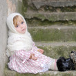 The small sad girl in a white scarf sits on a ladder - Stock Photo