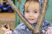 The small beautiful girl in a dark blue scarf near a tree — Stock Photo