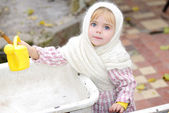 Portrait of the small beautiful girl in a white scarf with a watering can — Stock Photo