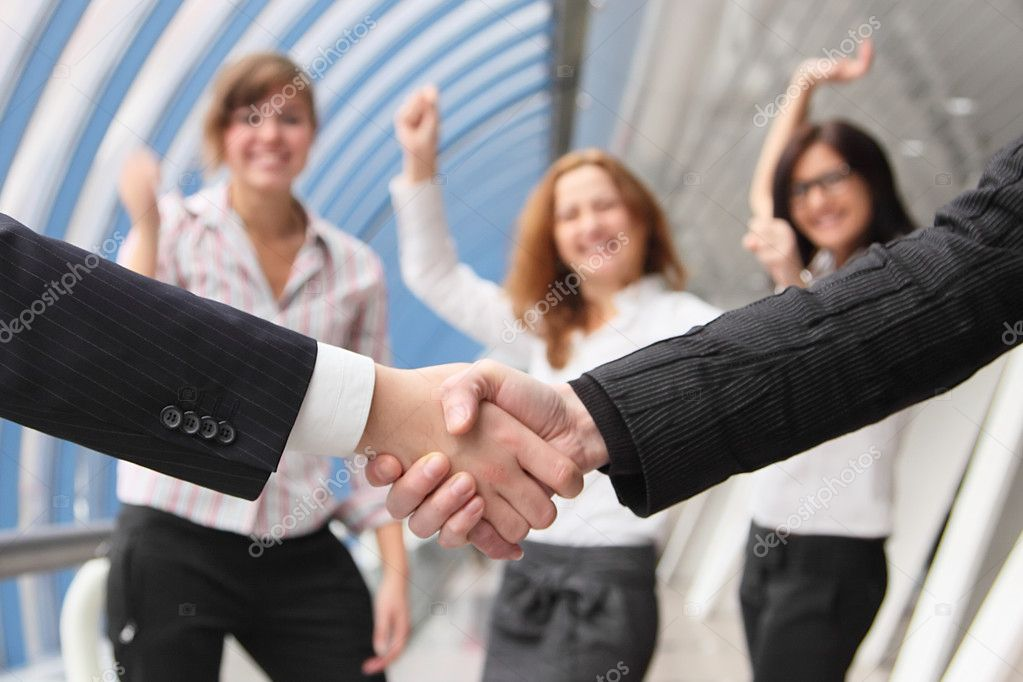 Hand shake of two businessmen against happy colleagues — Stock Photo #7172441