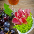 Royalty-Free Stock Photo: Pepper salami and bunches of grapes