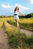 Young happy girl walking in meadow — Stock Photo