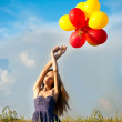 Beautiful young girl in a field holding a lot of colorful balloons — Stock Photo