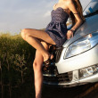 Sexy young beautiful girl in short dress lying on hood of car — Stock Photo #7180086