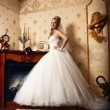 Beautiful young bride stands in the antique interior — Stock Photo