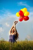 Schöne junge mädchen in einem feld mit vielen bunten luftballons — Stockfoto