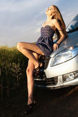 Sexy young beautiful girl in a short dress lying on the hood of car — Stock Photo