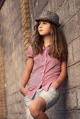 Portrait of a beautiful young girl teenager who stands against the wall in — Stock Photo