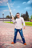Man having fun and holding a tripod from the camera — Stock Photo