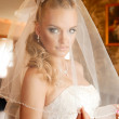 A young bride in a wedding gown dresses veil at home — Stock Photo