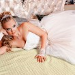 Bride lying on a bed in a wedding dress on their wedding night — Stock Photo