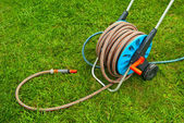 Hose for watering the garden on the green grass — Stock Photo