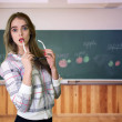 Pretty amazed young teacher in front of a blackboard. — Stock Photo
