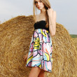 A beautiful young girl in a dress stands near haystack of hay in the field — Stock Photo
