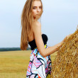 A beautiful young girl in a dress stands near haystack of hay in the field — Stock Photo #7540389