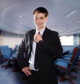 улыбающийся молодой бизнесмен корректирует его галстук в офисе — Стоковое фото