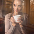 Beautiful woman drinking coffee in the morning sitting by the window - Stockfoto