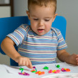Boy and flowers of plasticine — Stock Photo