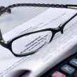 Stock Photo: Tax document with calculator and glasses