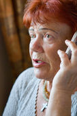 Frightened senior woman with cellphone — Stock Photo