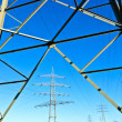 Steel electricity pylon on bright blue sky - Stock fotografie