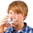Boy drinking water out of a glass — Stockfoto