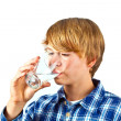 Boy drinking water out of a glass — Stock fotografie