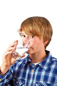 Boy drinking water out of a glass — Stock Photo