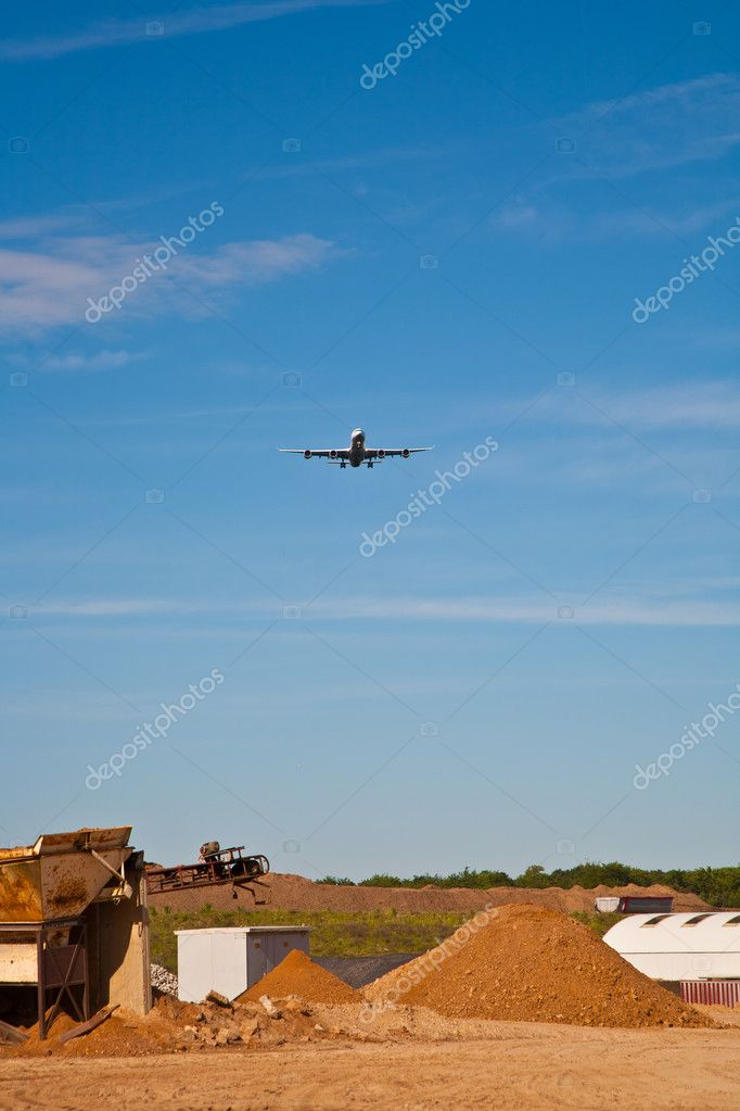 Conveyor on site at gravel pit hill with overflying aircraft in approach — Stock Photo #6818850