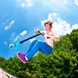 Stock Photo: Young boy going airborne with a scooter