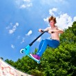 Young boy going airborne with a scooter — Stock Photo #6864600