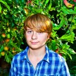 Portrait of cute boy in leaves — Stock Photo #6929829