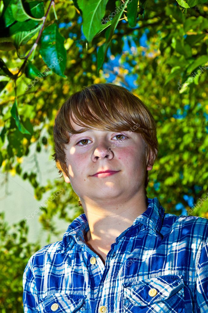 Portrait of cute boy in leaves of the tree — Stock Photo #6929855