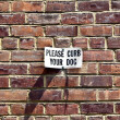 Sign please curb your dog at a house wall — Stock Photo
