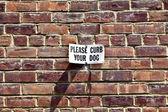 Signe s'il vous plaît freiner votre chien à un mur de maison — Photo