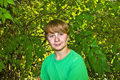 Cute smart boy in the garden under the tree — Stockfoto