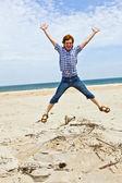 Jongen geniet van het prachtige strand en springt — Stockfoto