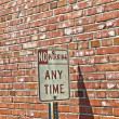 No parking sign in front of brick wall — Foto de Stock