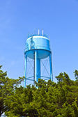 A blue watertower against a blue cloudy sky — Stock Photo