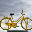 Old yellow bike on roof as hint for bike ferry in dark cloud — Stock Photo #7153729
