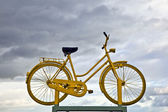 Old yellow bike on a roof as hint for a bike ferry in dark cloud — Stock Photo